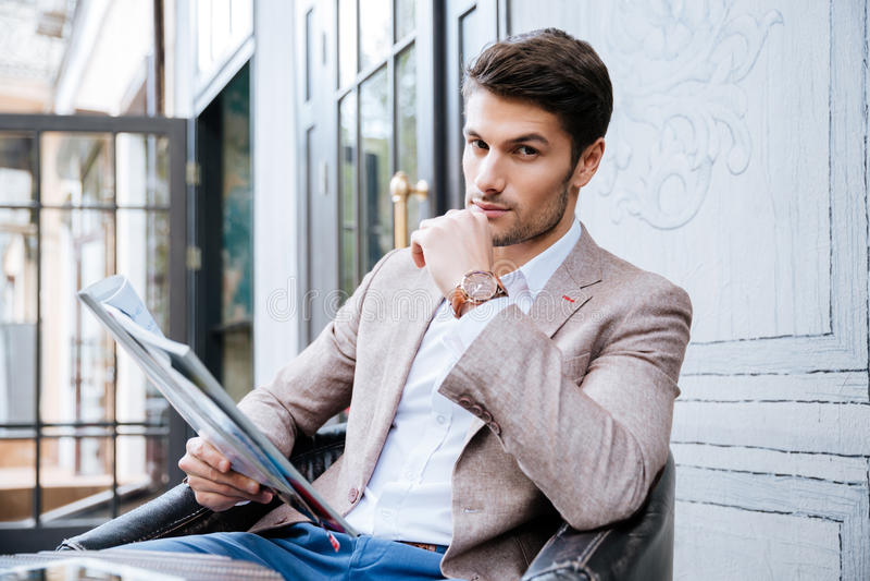 Hombre de negocios hermoso joven que lee un periódico en cafetería imágenes de archivo libres de regalías