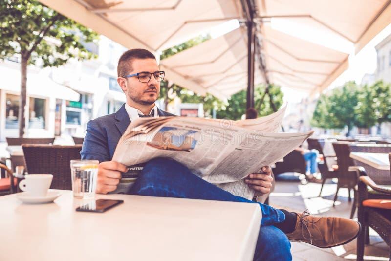 Hombre de negocios hermoso joven que lee un peri?dico foto de archivo libre de regalías