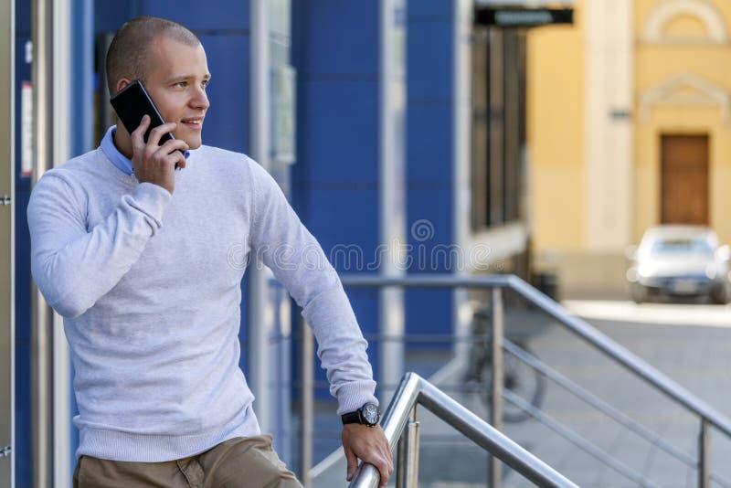 Hombre de negocios hermoso joven que se coloca delante del edificio y fotos de archivo