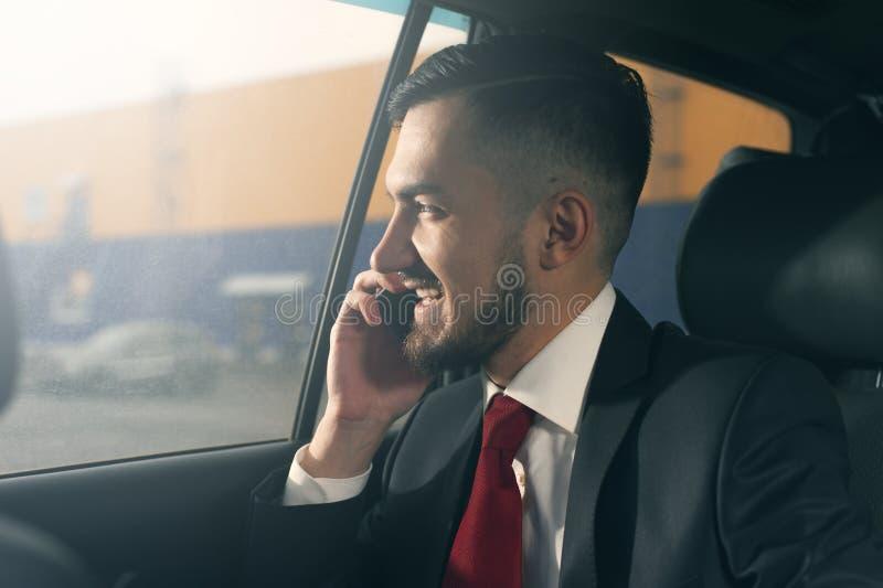 Hombre de negocios hermoso joven que se sienta en el coche fotos de archivo libres de regalías