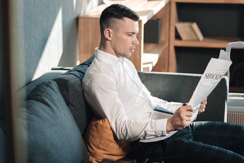 Hombre de negocios hermoso joven que se sienta en el periódico de la lectura del sofá fotografía de archivo libre de regalías