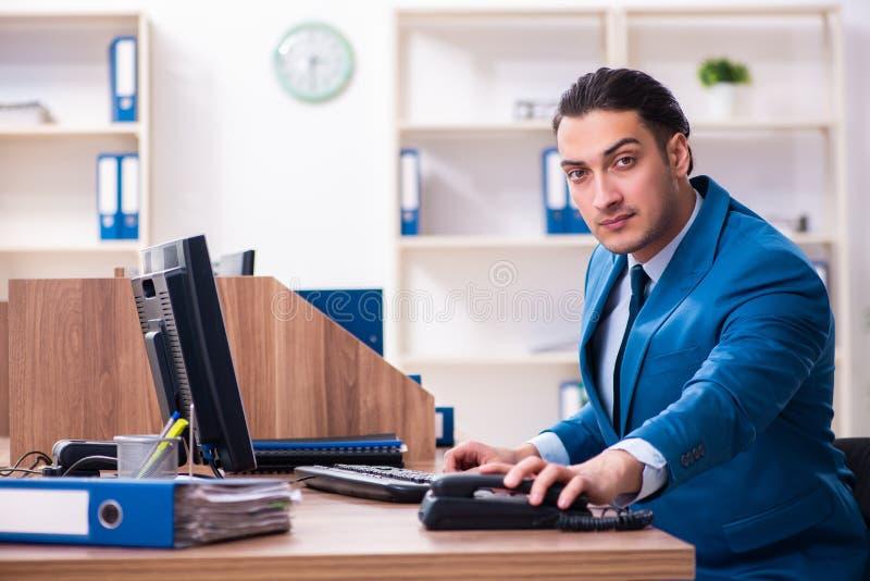 Hombre de negocios hermoso joven que se sienta en la oficina foto de archivo