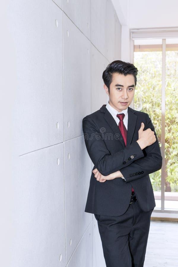 Hombre de negocios hermoso joven que sonríe y elegante en la oficina Él es 20-30 años fotografía de archivo