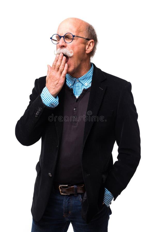 Hombre de negocios hermoso mayor que bosteza en el fondo blanco imagen de archivo libre de regalías