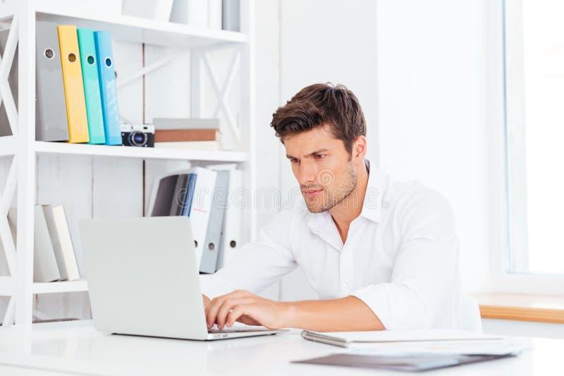 Hombre de negocios hermoso pensativo joven que se sienta en la tabla con el ordenador portátil imagen de archivo libre de regalías