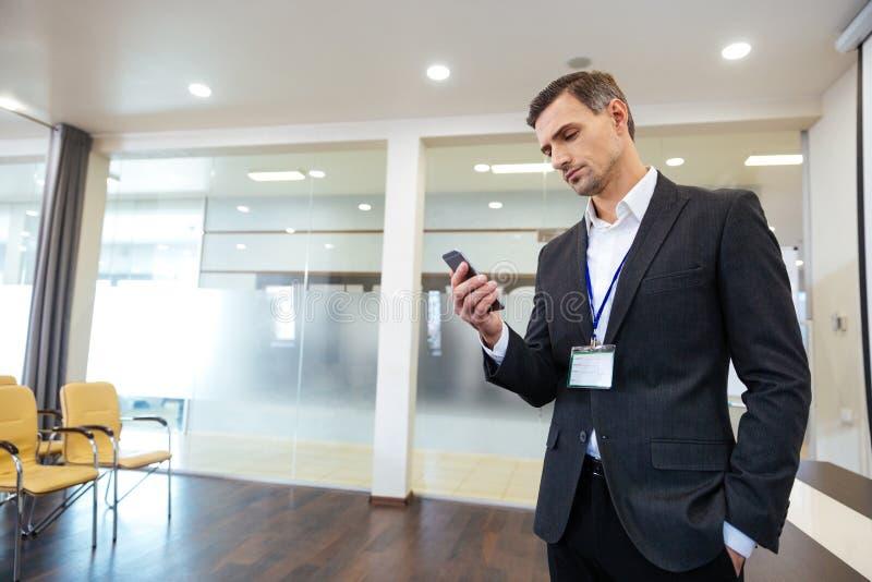 Hombre de negocios hermoso pensativo que usa el teléfono celular fotografía de archivo