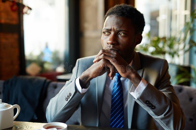 Hombre de negocios hermoso preocupante en café imagen de archivo