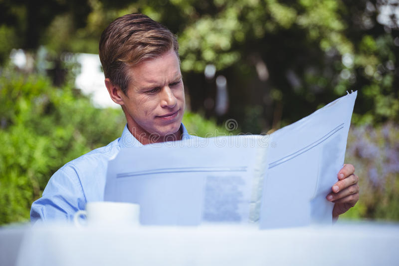 Hombre de negocios hermoso que come café y que lee las noticias fotos de archivo
