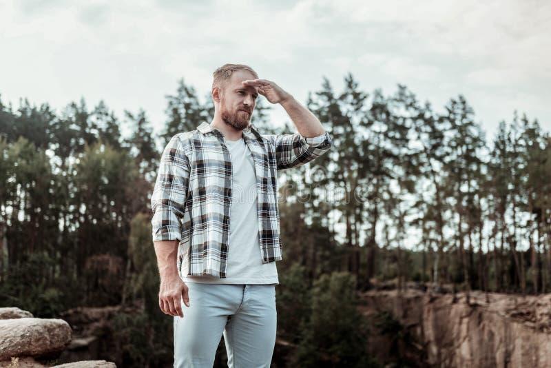 Hombre de negocios hermoso que concentra mientras que mira lejos en las montañas imagen de archivo