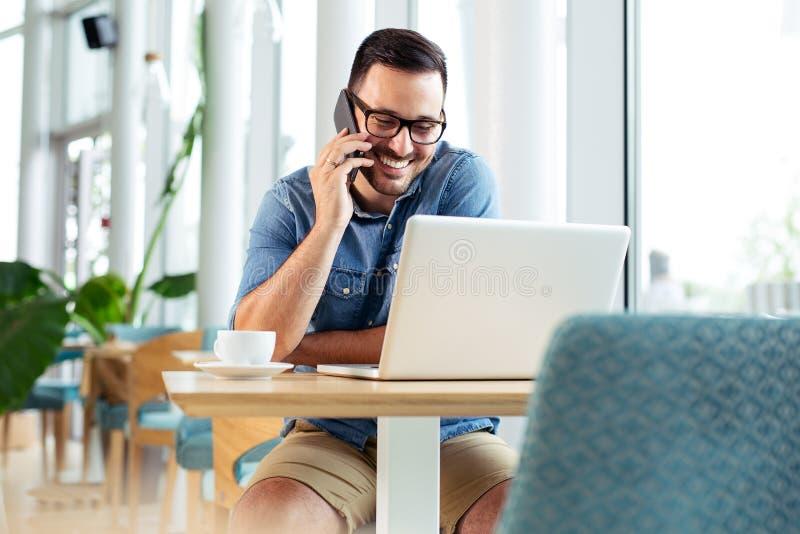 Hombre de negocios hermoso que habla en el teléfono en cafetería foto de archivo libre de regalías