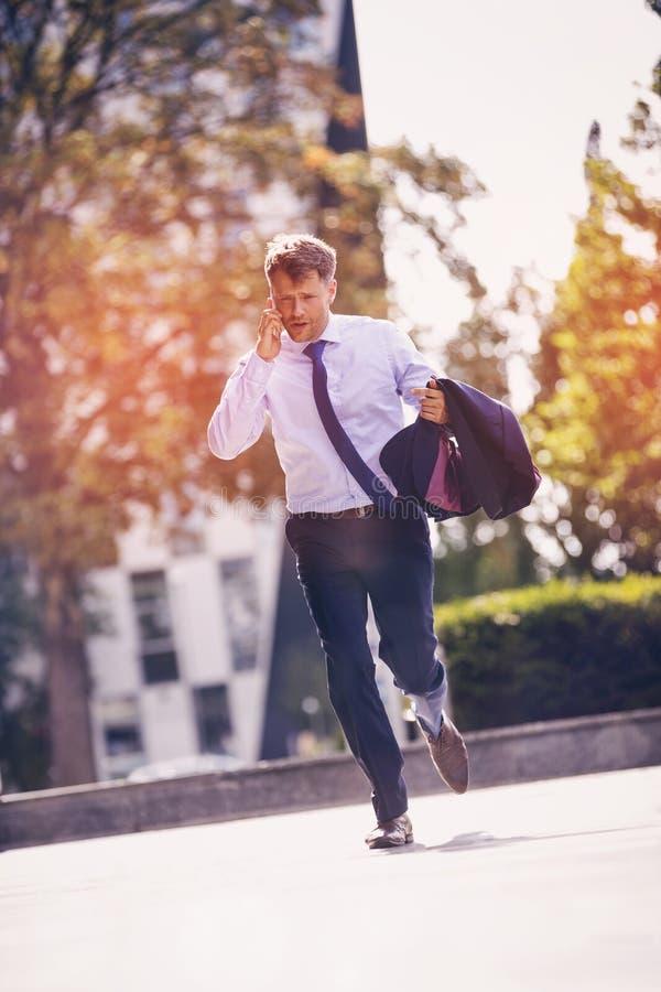 Hombre de negocios hermoso que habla en el teléfono móvil en la calle foto de archivo