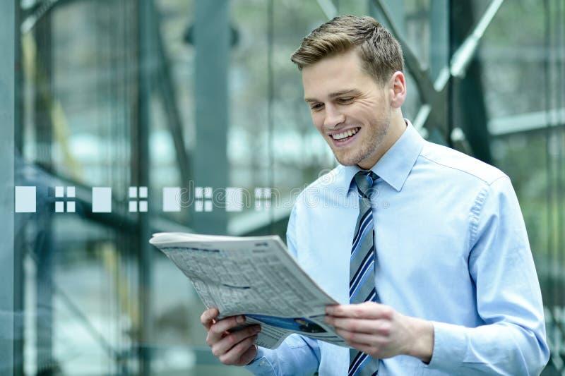 Hombre de negocios hermoso que lee un periódico foto de archivo