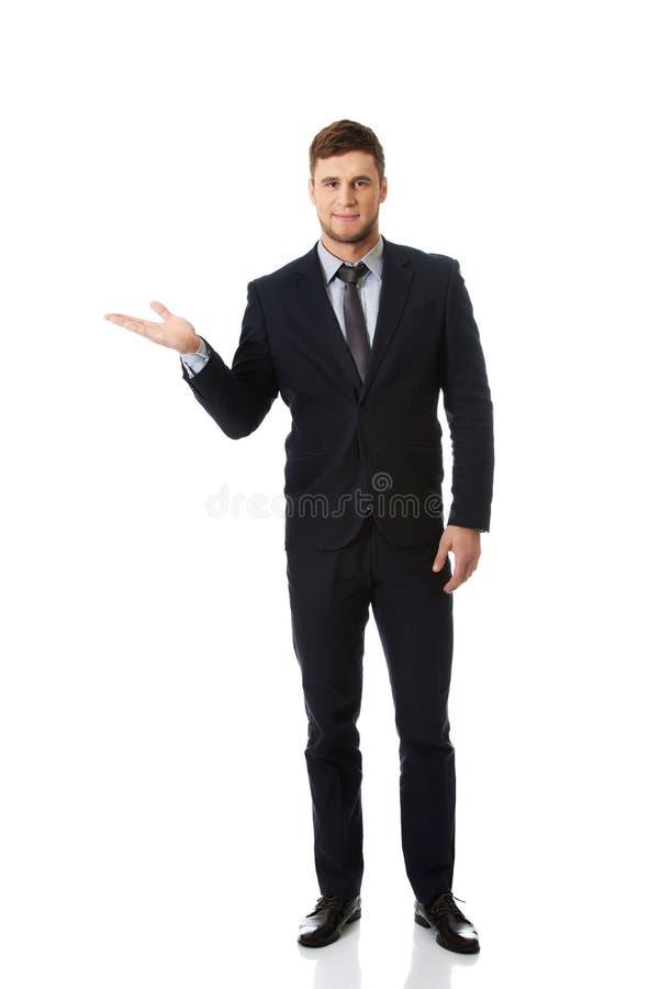 Hombre de negocios hermoso que lleva a cabo el copyspace en la palma imagen de archivo libre de regalías