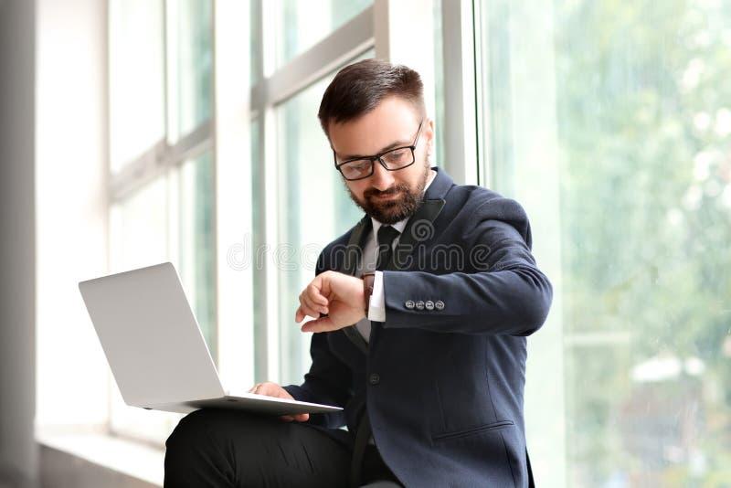 Hombre de negocios hermoso que mira el reloj mientras que trabaja con el ordenador portátil cerca de ventana imagen de archivo