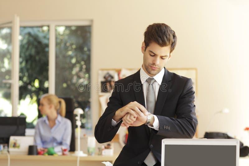 Hombre de negocios hermoso que mira su reloj imagen de archivo libre de regalías
