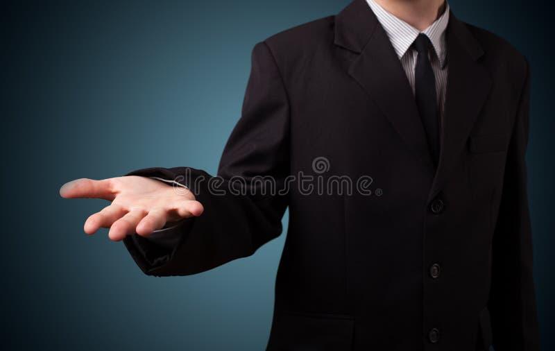 Hombre de negocios hermoso que presenta con el espacio de la copia de la mano imagen de archivo
