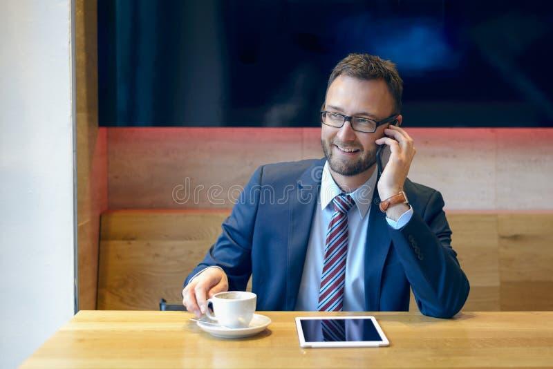 Hombre de negocios hermoso que se sienta en la tabla con café fotografía de archivo libre de regalías