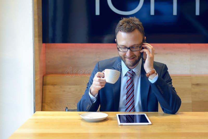 Hombre de negocios hermoso que se sienta en la tabla con café imagenes de archivo