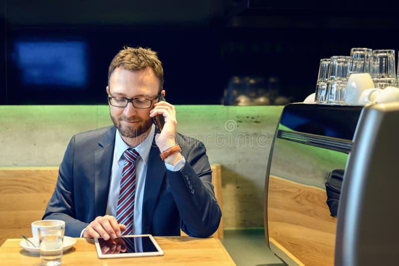 Hombre de negocios hermoso que se sienta en la tabla con café fotografía de archivo