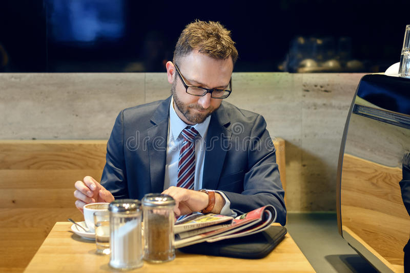 Hombre de negocios hermoso que se sienta en la tabla con la lectura del café imagenes de archivo