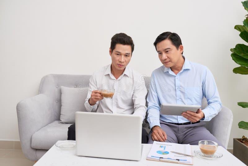 Hombre de negocios hermoso que sonr?e mientras que trabaja con un ordenador port?til en casa foto de archivo