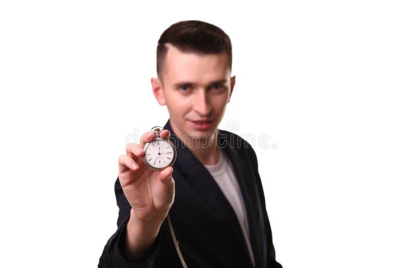Hombre de negocios hermoso que sostiene un reloj Sobre el fondo blanco foto de archivo libre de regalías