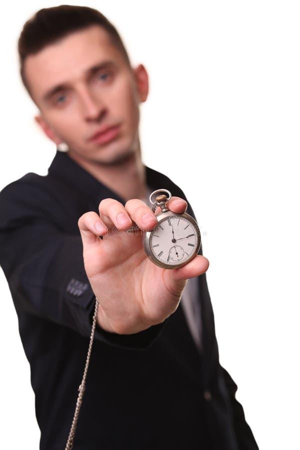 Hombre de negocios hermoso que sostiene un reloj Sobre el fondo blanco fotos de archivo libres de regalías