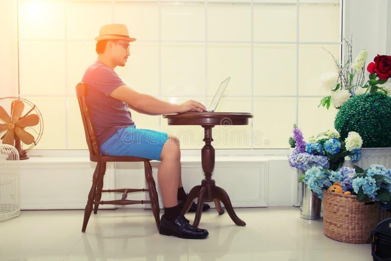 Hombre de negocios hermoso que trabaja con el ordenador portátil cerca de la ventana en imagenes de archivo
