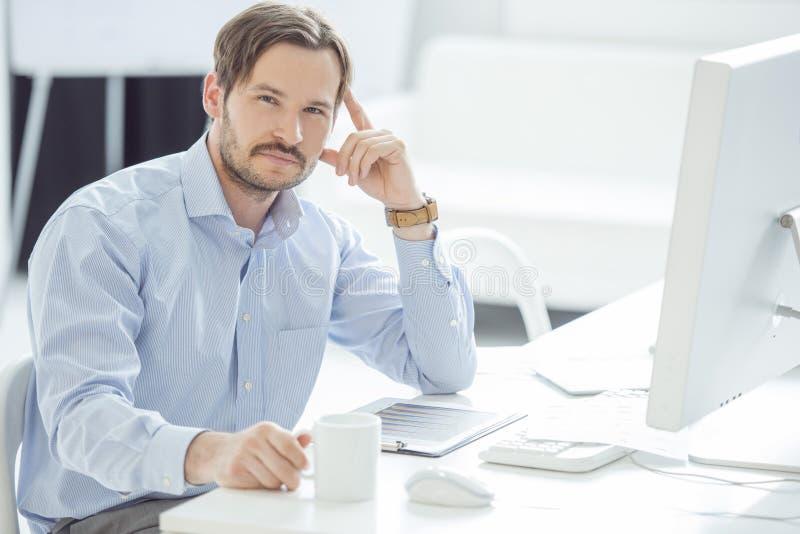 Hombre de negocios hermoso que trabaja en su escritorio imagen de archivo