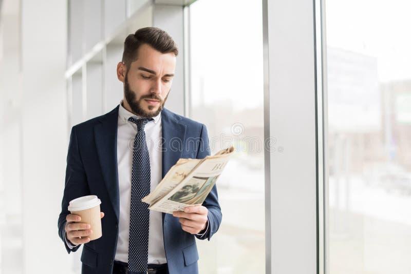 Hombre de negocios hermoso Reading Newspaper por la ventana imagen de archivo libre de regalías