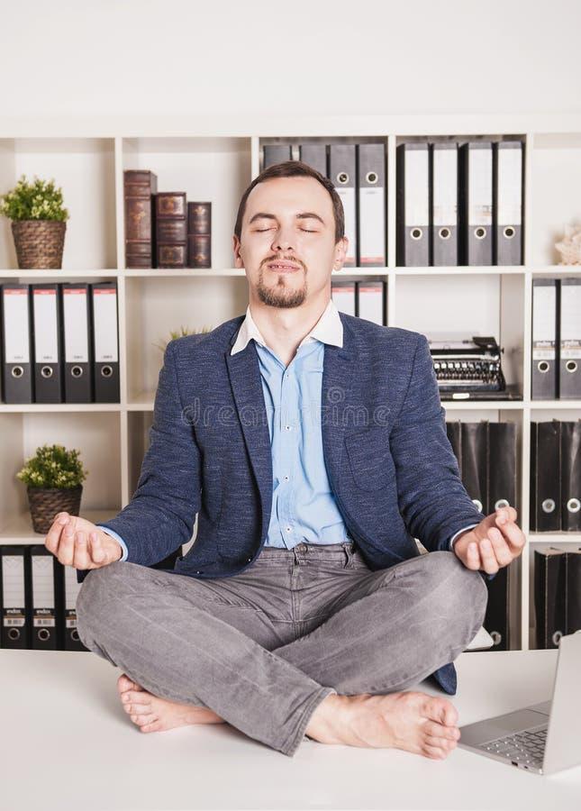Hombre de negocios hermoso relajarse en actitud del loto en oficina foto de archivo libre de regalías