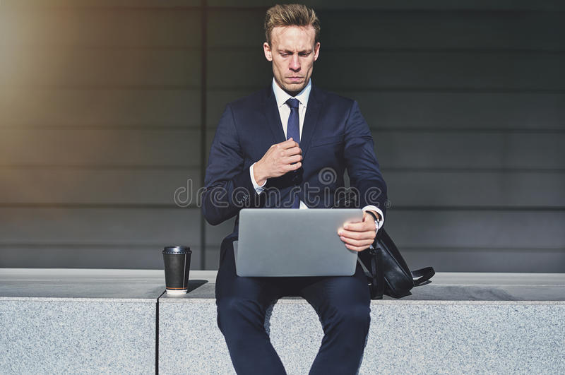 Hombre de negocios hermoso serio que gira su ordenador portátil fotos de archivo libres de regalías
