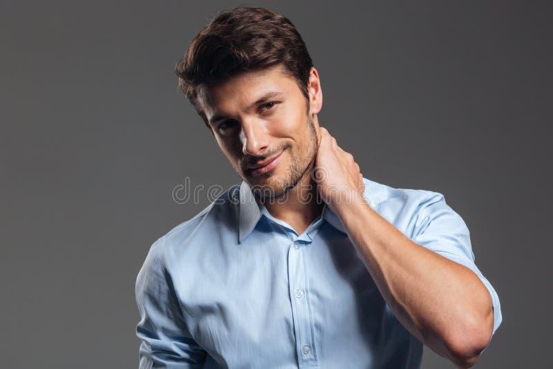 Hombre de negocios hermoso sonriente pensativo en la camisa blanca que mira la cámara imagenes de archivo
