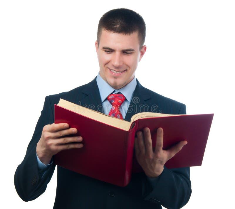 Hombre de negocios hermoso sonriente que lee el libro imágenes de archivo libres de regalías