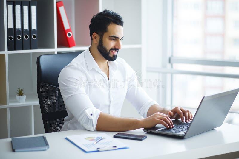 Hombre de negocios hermoso Working en el ordenador portátil en su oficina fotografía de archivo