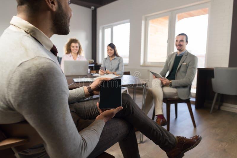 Hombre de negocios hispánico que lleva a cabo al grupo en blanco de los empresarios de la tableta en la raza diversa de centro Te fotografía de archivo libre de regalías