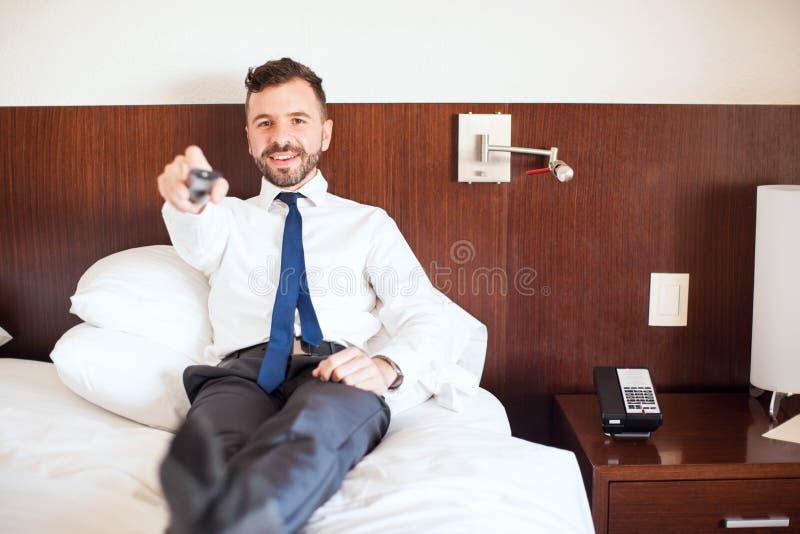 Hombre de negocios hispánico que ve la TV en un hotel imágenes de archivo libres de regalías