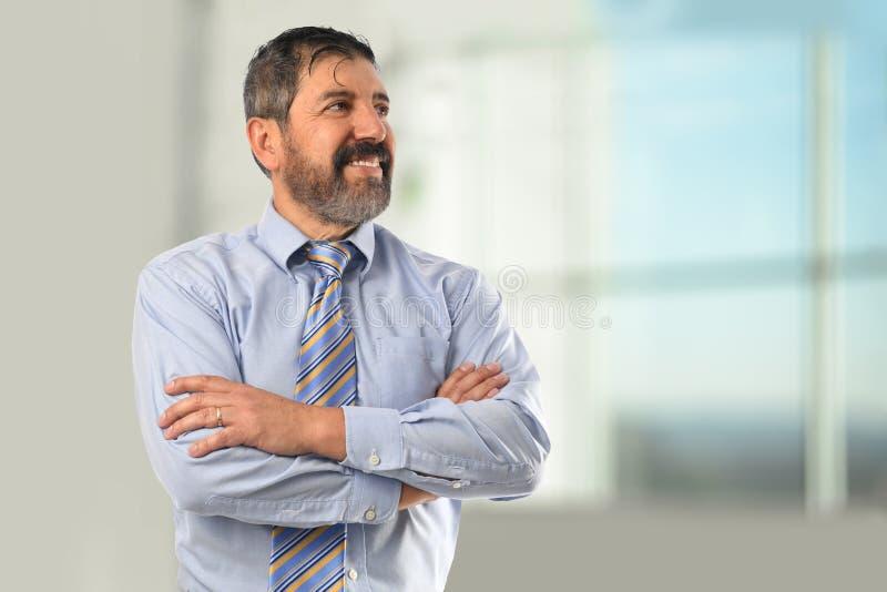 Hombre de negocios hispánico Smiling con los brazos cruzados fotografía de archivo libre de regalías