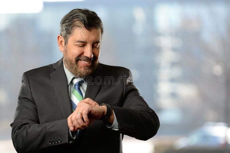 Hombre de negocios hispánico Using Electronic Watch foto de archivo libre de regalías