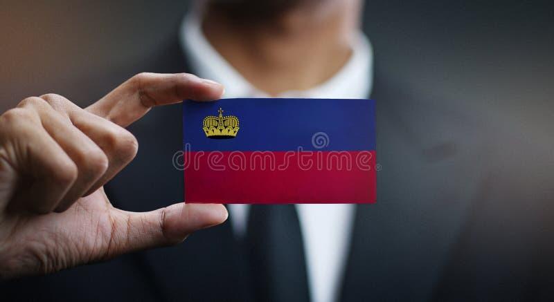 Hombre de negocios Holding Card de la bandera de Liechtenstein imágenes de archivo libres de regalías