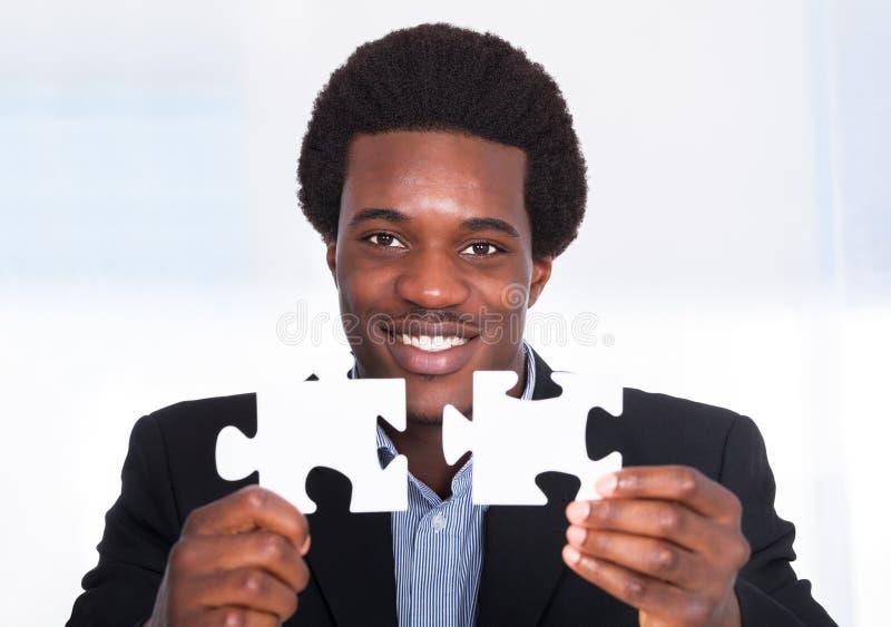 Hombre de negocios Holding Jigsaw Puzzle fotos de archivo libres de regalías