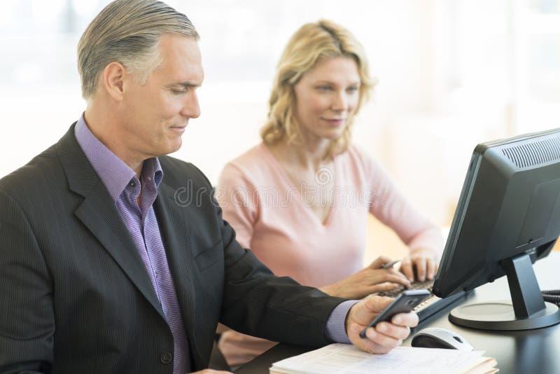 Hombre de negocios Holding Mobile Phone mientras que colega que usa el ordenador imágenes de archivo libres de regalías