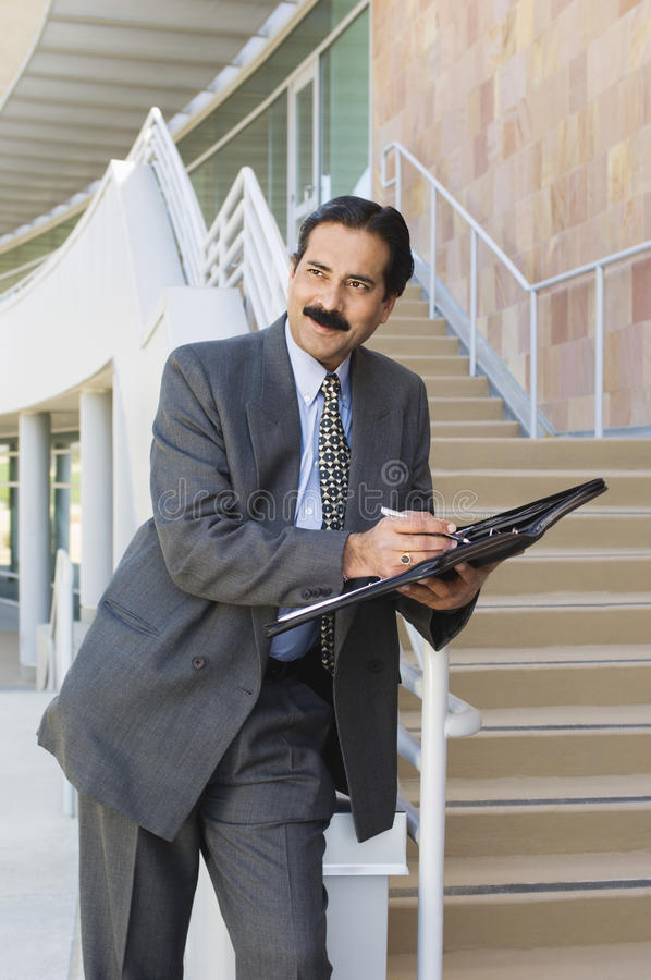 Hombre de negocios Holding Daily Organizer imagen de archivo libre de regalías