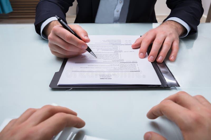 Hombre de negocios Holding Pen Over Resume foto de archivo libre de regalías