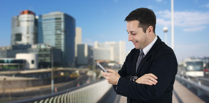 Hombre de negocios Holding Phone While que sonríe y que siente feliz con la ciudad del negocio y los edificios corporativos en fo fotografía de archivo libre de regalías