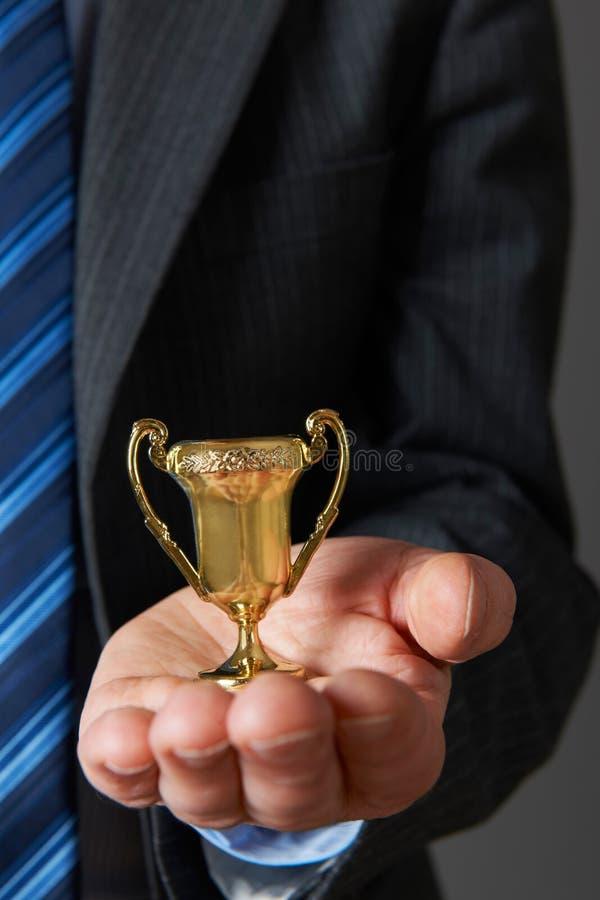 Hombre de negocios Holding Small Trophy fotos de archivo libres de regalías