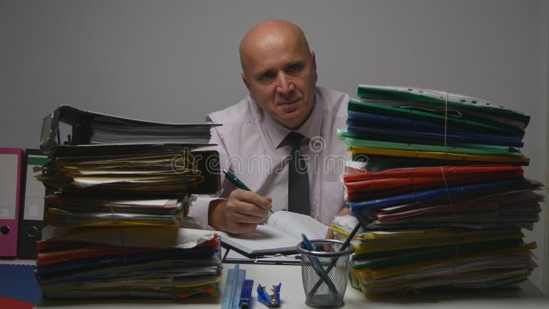 Hombre de negocios Image Smiling y funcionamiento en documentos de cuenta del sitio del archivo fotografía de archivo libre de regalías