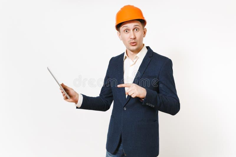 Hombre de negocios impresionado hermoso joven en el traje oscuro, casco de protección protector señalando el dedo índice en el or imagen de archivo libre de regalías