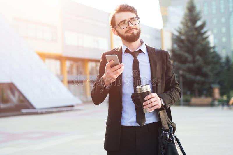 Hombre de negocios impresionado inconformista que usa smartphone en fondo de la estructura de la oficina con el bolso disponible  imagen de archivo