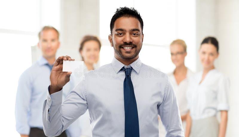 Hombre de negocios indio con la tarjeta de visita en la oficina imagen de archivo